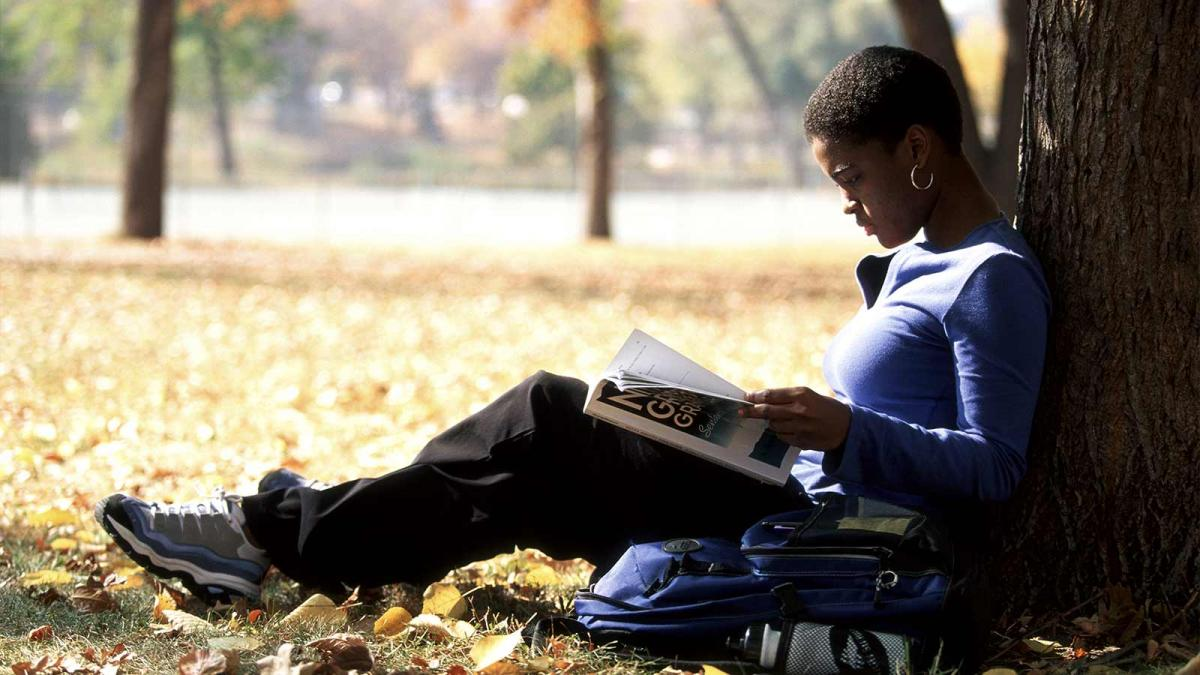 student reading a textbook while leaning against a tree.