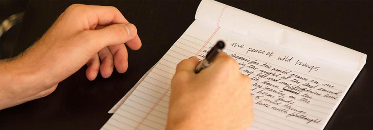 a right-handed person writing a short story on a tablet of paper